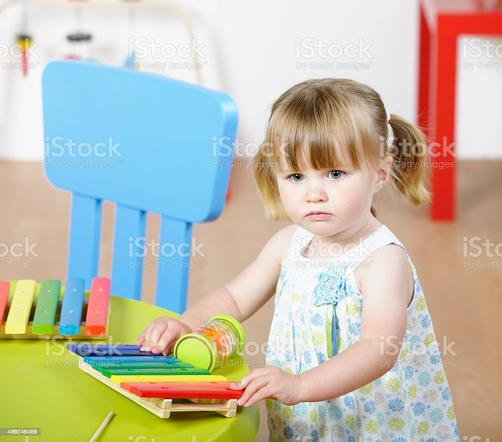 Toddler Holding A Xylophone In A Nursery stock photo