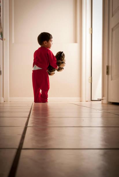 Toddler holding toy standing in hallway looking through door stock photo