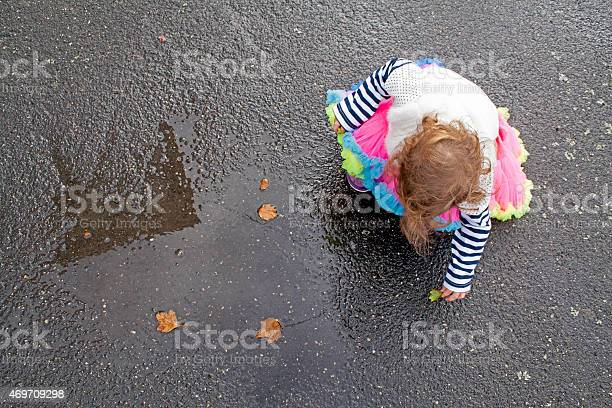 Photo of Toddler in Bright Clothes Playing with leaves in Rain Puddle