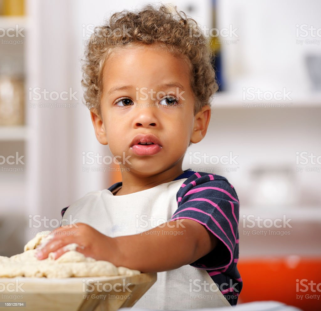 Toddler In Deep Thought While Preparing Dough royalty-free stock photo