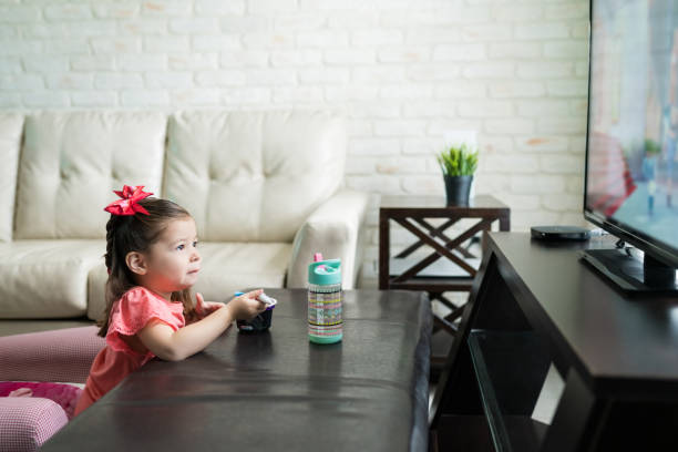 Toddler Is Enjoying TV And Food At Home Little kid having breakfast while watching TV in living room at home cartoon and kids stock pictures, royalty-free photos & images
