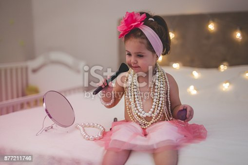 istock Toddler is putting mother's make up on a face 877211746