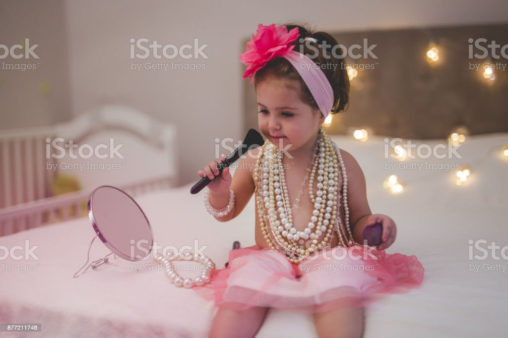 Toddler is putting mother's make up on a face stock photo