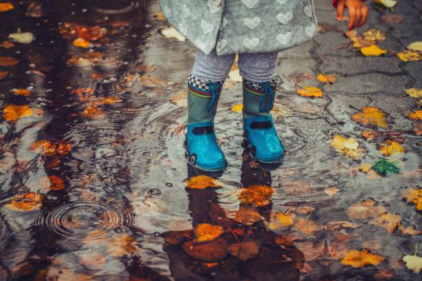 kleinkind sprung ins wasserbecken der herbsttag - kinder winterstiefel stock-fotos und bilder