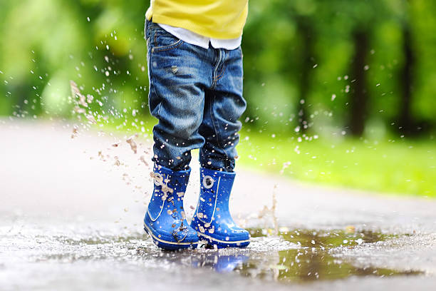 Toddler jumping in pool of water stock photo