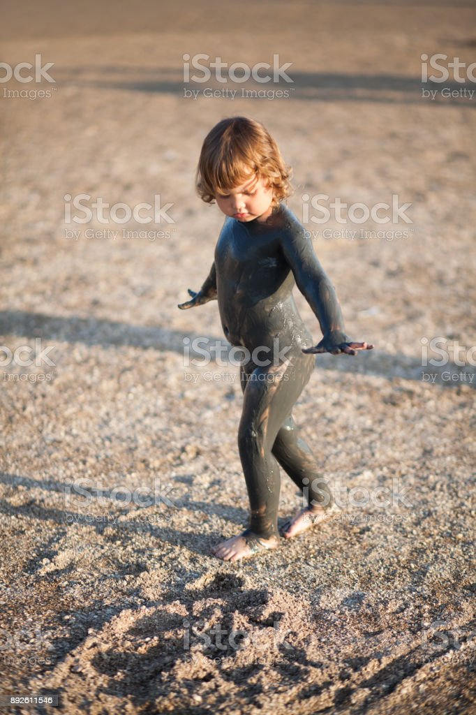 Toddler kid covered with black health mud outdoor, copyspace. stock photo