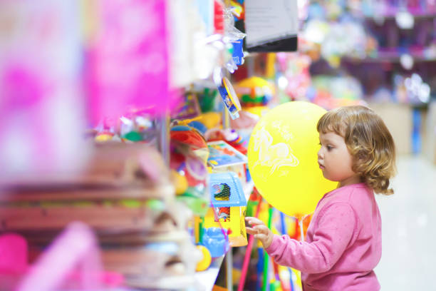 Toddler kid shopper at the toy shop. stock photo