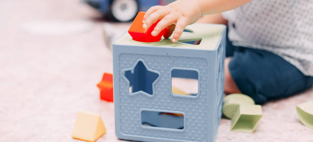 toddler kid solves sorter puzzle block at home - shape stock pictures, royalty-free photos & images