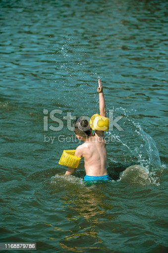 istock toddler kid swimming in sea water outdoors with inflatable arms aids on his hands 1168879786