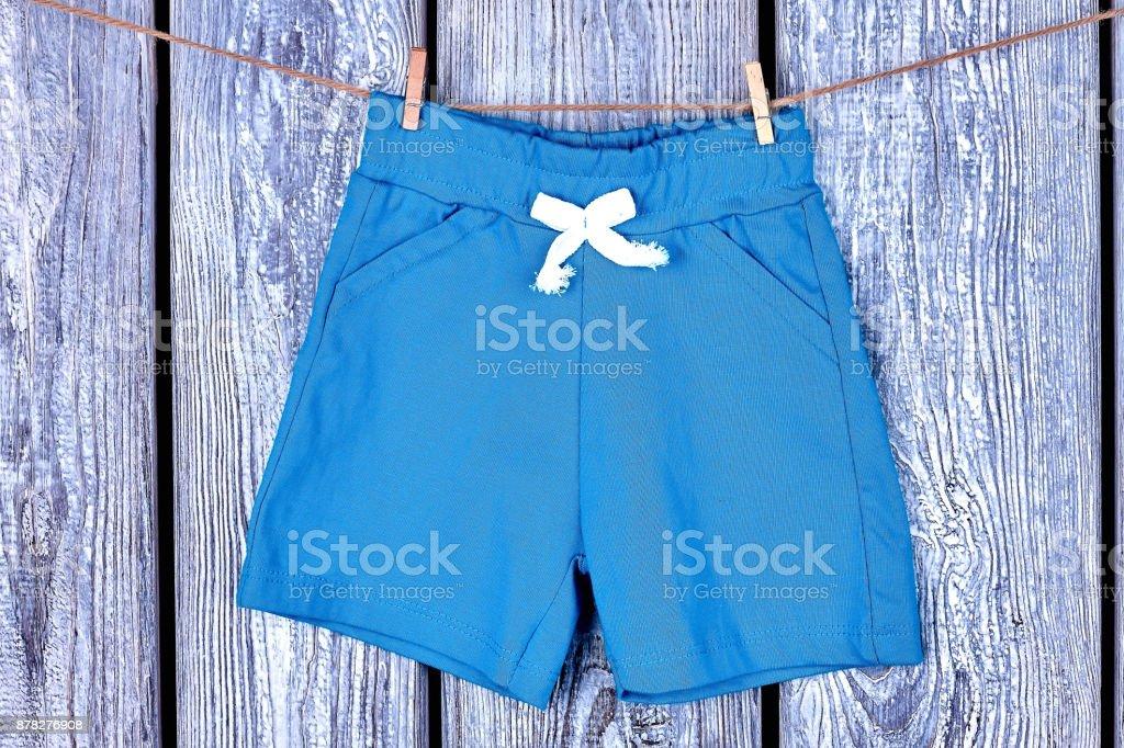 Toddler kids shorts hanging on rope. stock photo