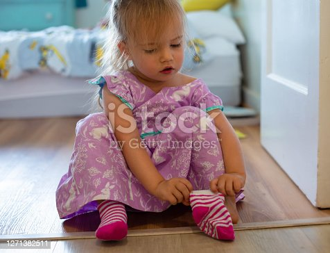 A litte girl sitting in her bedroom trying to put on her socks to get ready to leave the house.