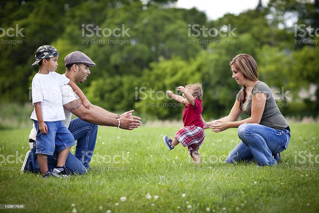 Toddler Learning to Walk with Happy Family Outside stock photo