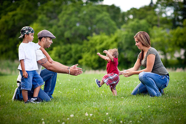 toddler learning to walk with happy family outside - first step stock photos and pictures