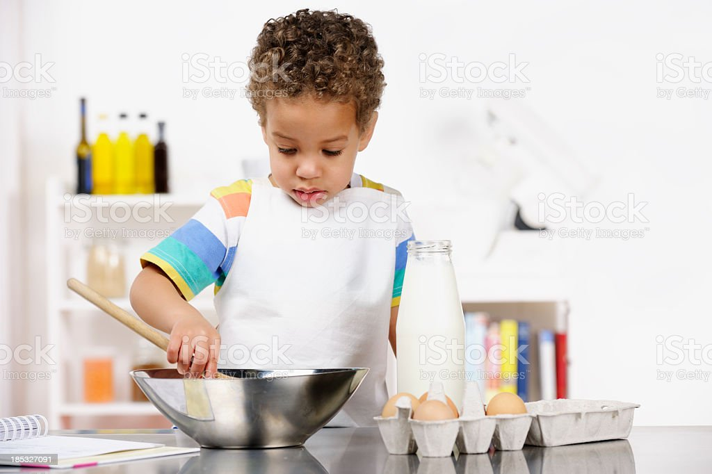Toddler/ Little Boy Preparing Food In the Kitchen stock photo