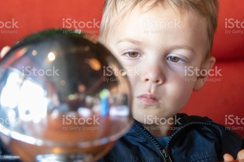 male caucasian toddler looking to a metallic sphere