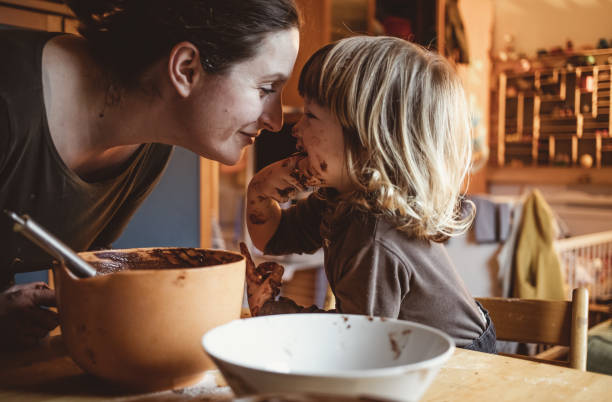 toddler making cookies with his mother - cioccolata foto e immagini stock