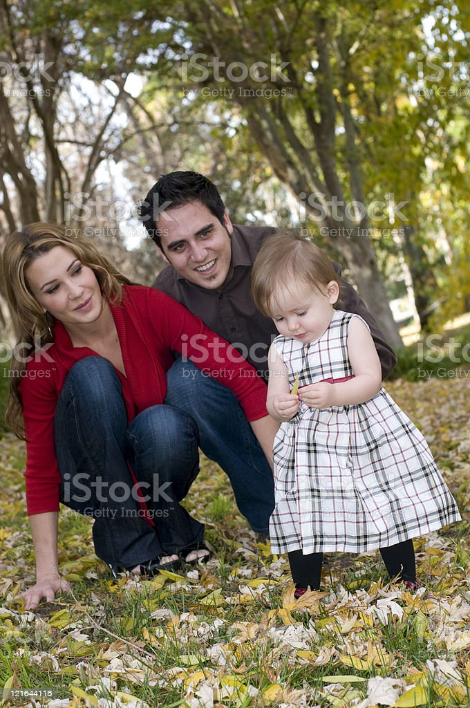 Toddler, Mom, and Dad Play in a Park During Autumn royalty-free stock photo