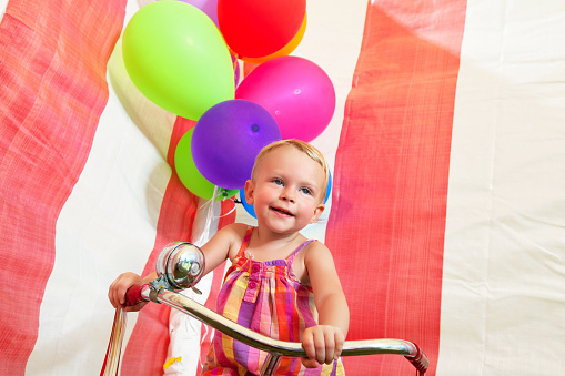 istock Toddler on tricycle with ballons 483168313