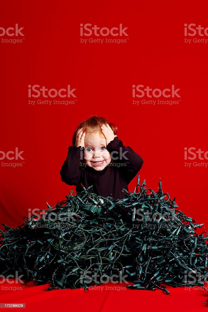 Toddler Overwhelmed by Pile of Tangled Christmas Lights royalty-free stock photo