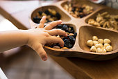 Child hand picking almonds from a wooden bowl with mixed nuts and dried fruits.