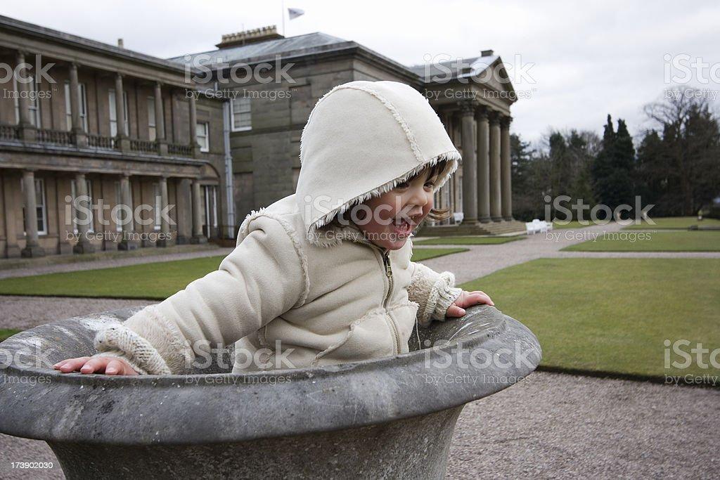 Toddler playing in garden urn royalty-free stock photo