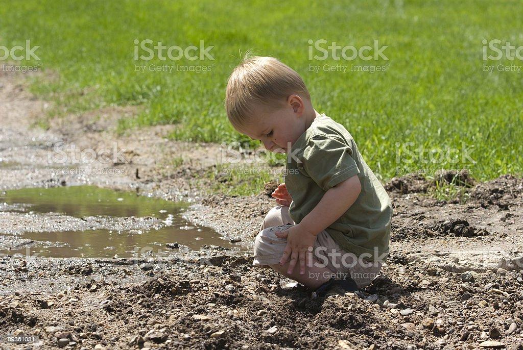 Toddler playing in mud royalty free stockfoto