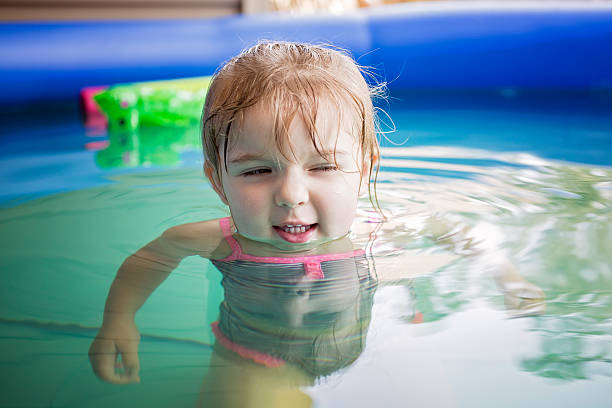 Toddler Playing in pool with a silly face stock photo
