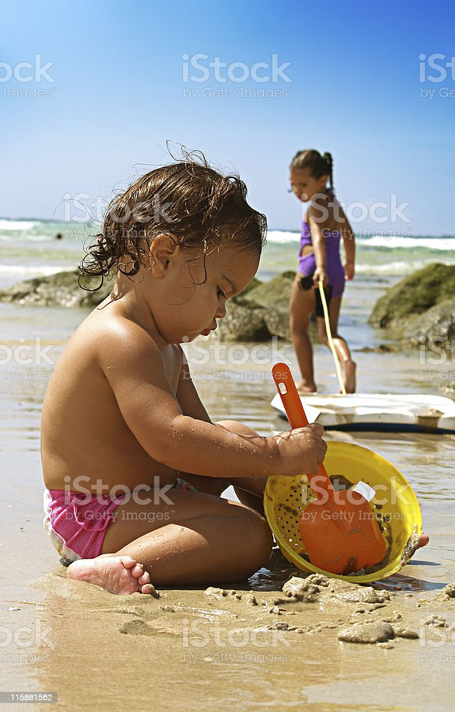 Toddler playing in the sand at the beach on a sunny day royalty-free stock photo
