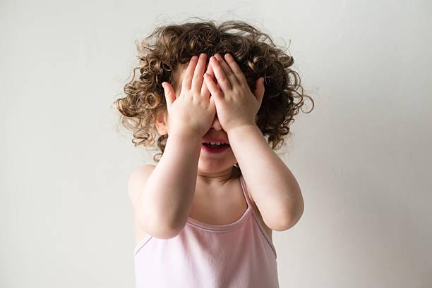 Toddler playing peekaboo stock photo
