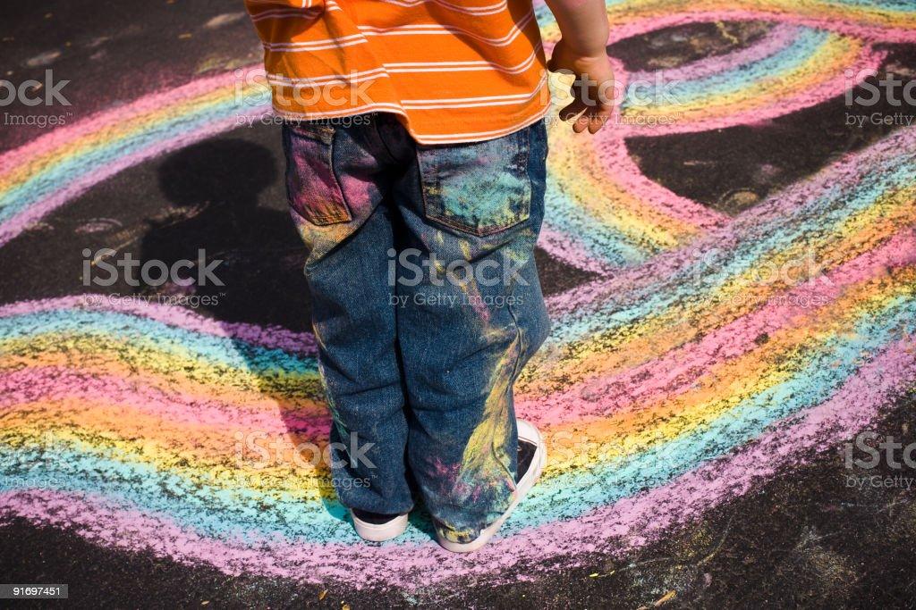 Toddler Playing Walking Along Colorful Chalk Paths on Asphalt royalty-free stock photo