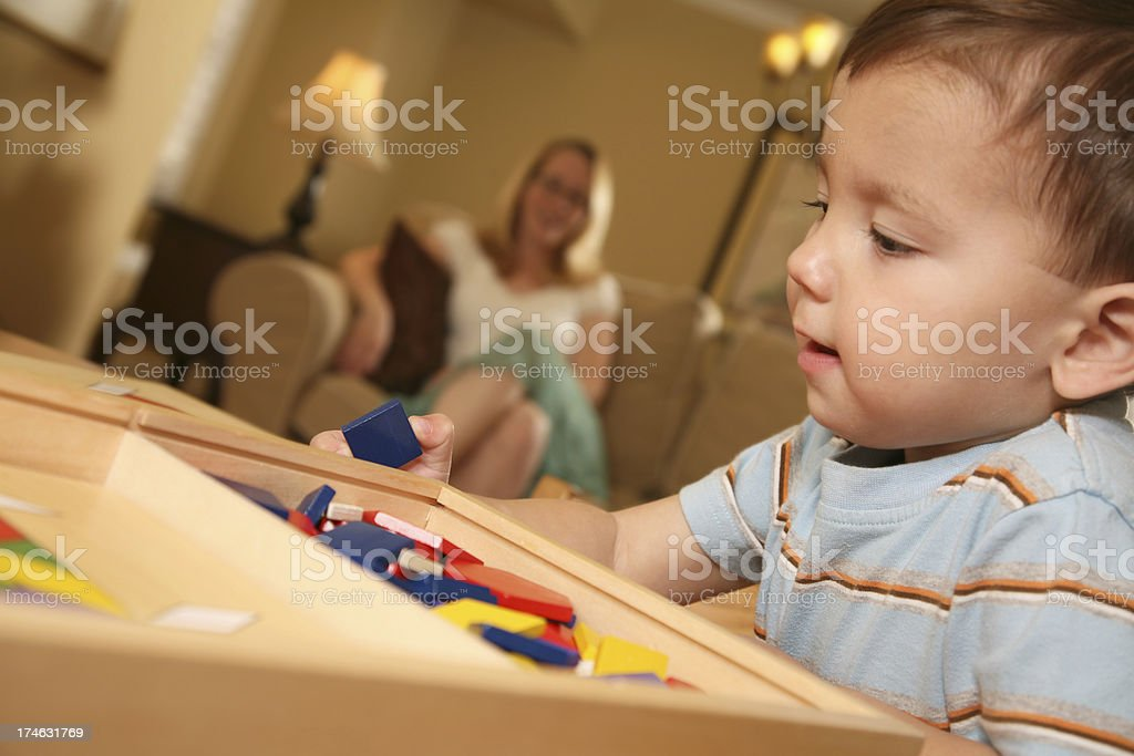 Toddler Playing with Blocks while mother looks on royalty-free stock photo