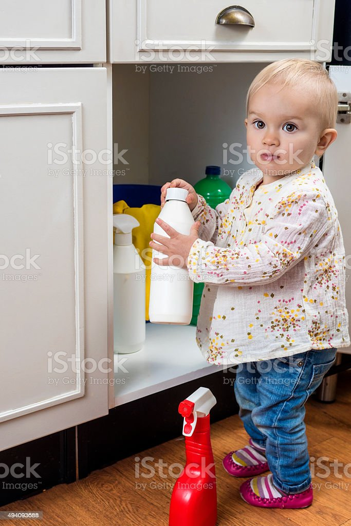 Toddler playing with cleaning products stock photo