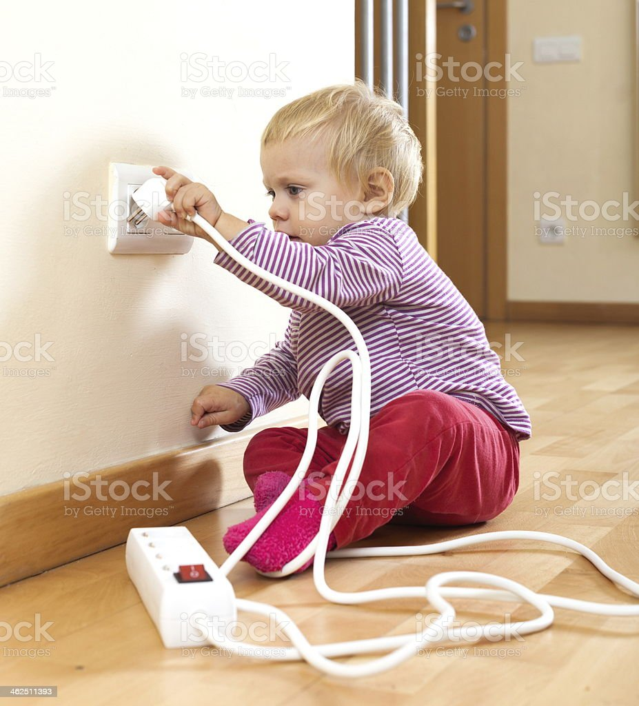 Toddler Playing With Electricity At Home Stock Photo