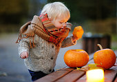 Toddler playing with halloween pumpkins