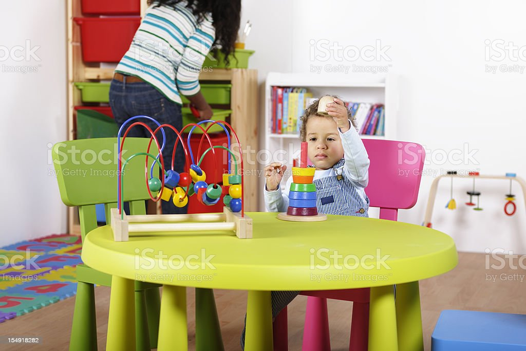 Toddler Playing With Multi-coloured Rings While Carer Tidies royalty-free stock photo