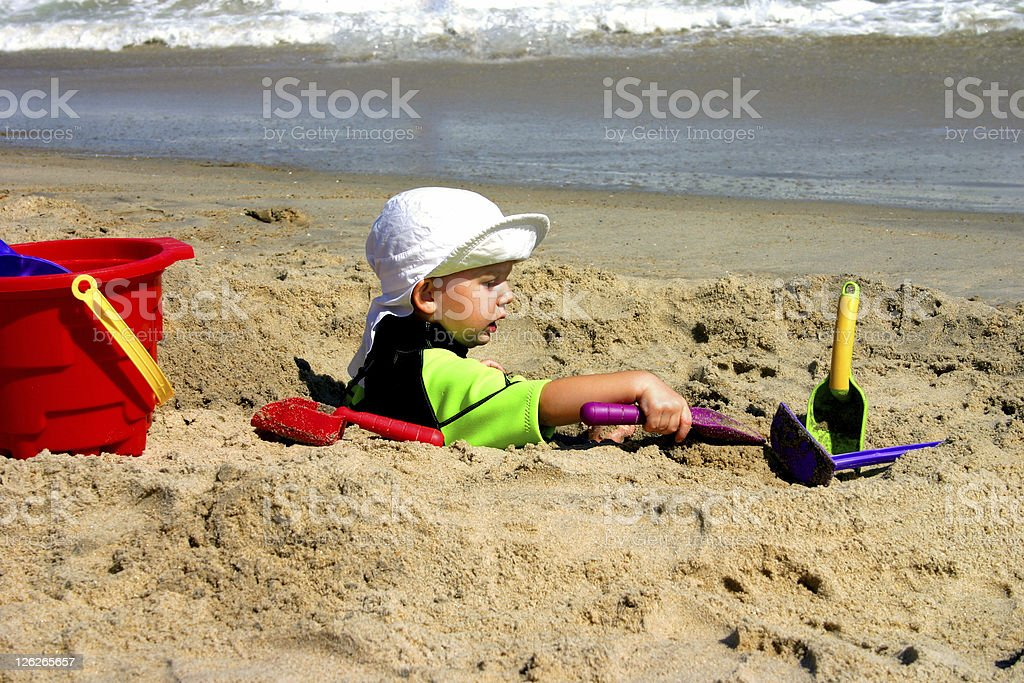Toddler playing with sand at the beach royalty-free stock photo