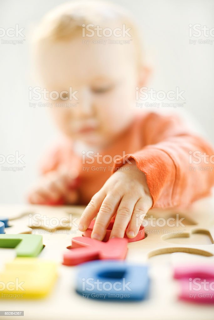 toddler playing with wooden letters royalty-free stock photo