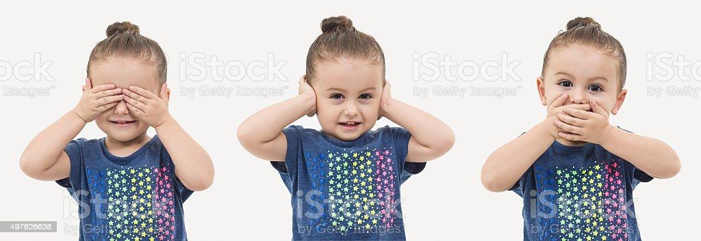 Toddler posing like three wise monkeys stock photo