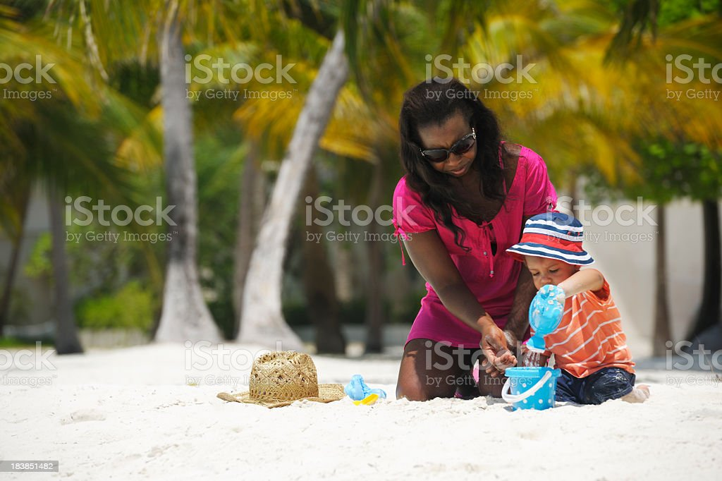 Toddler Pouring Water In Sand Bucket At  The Beach royalty-free stock photo