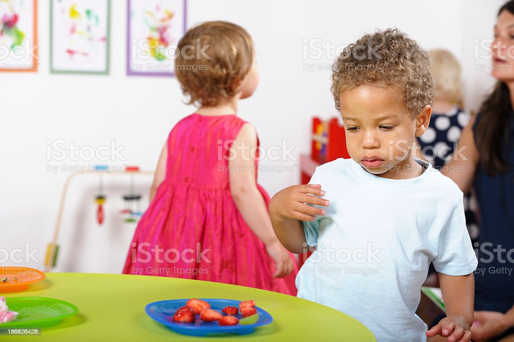 Toddler Relunctantly Looking A Plate Of Stawberries royalty-free stock photo