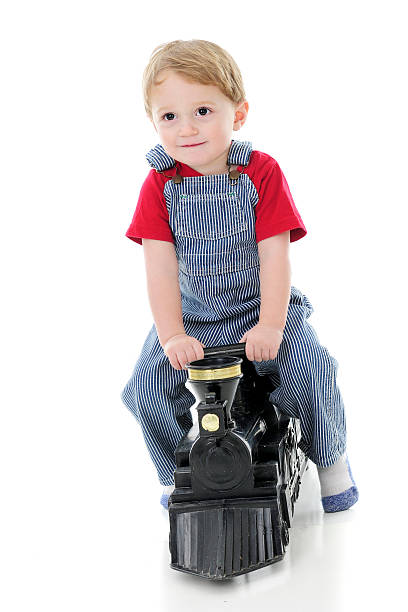 Toddler Riding the Rails An adorable 2-year-old dressed as a train engineer, happily riding a toy train engine.  On a white background. bib overalls boy stock pictures, royalty-free photos & images