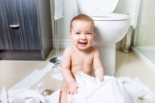 Bebê ripping para papel higiênico no banheiro - foto de acervo