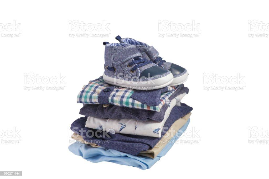Sapatos de criança e a pilha de roupas isolado no branco - foto de acervo