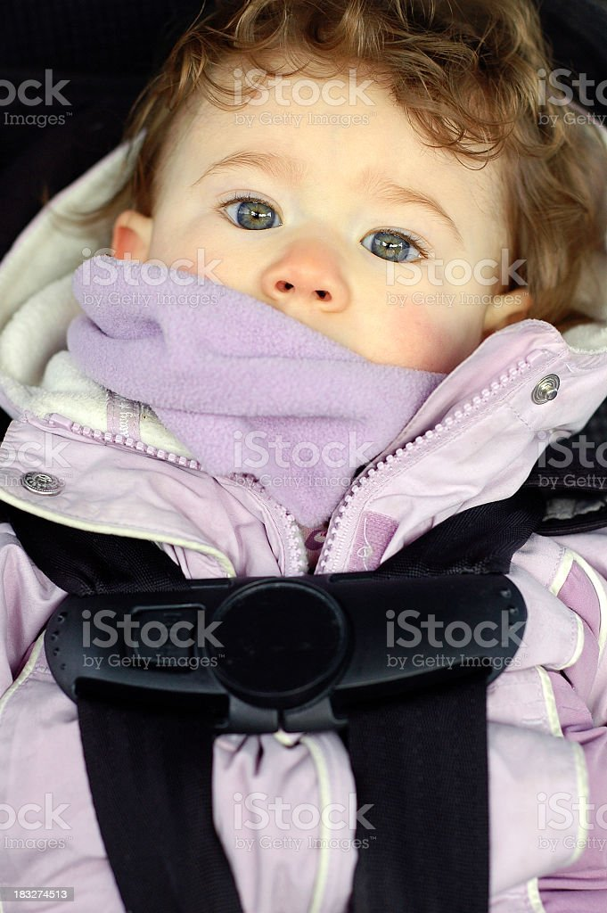 Toddler Sitting in Car Seat Bundled Up For Winter Weather stock photo