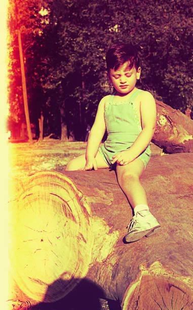 toddler sitting on a tree trunk - viagens anos 70 imagens e fotografias de stock