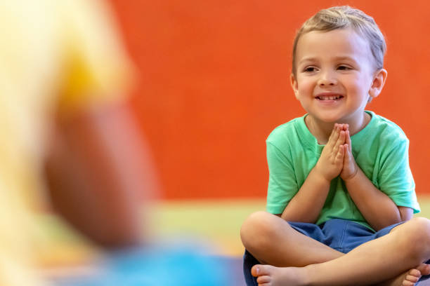 Toddler sitting on the floor at children yoga class stock photo