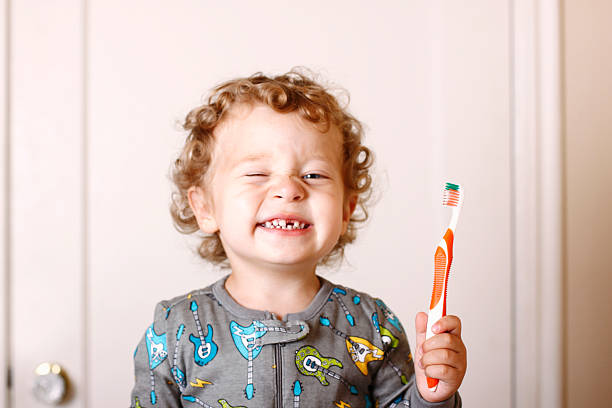 Toddler smiling while holding a toothbrush