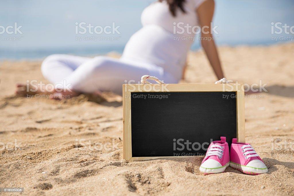 Chaussures pour jeunes enfants et mini tableau noir sur le sable - Photo