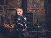 A toddler is standing by a log burner holding a shovel