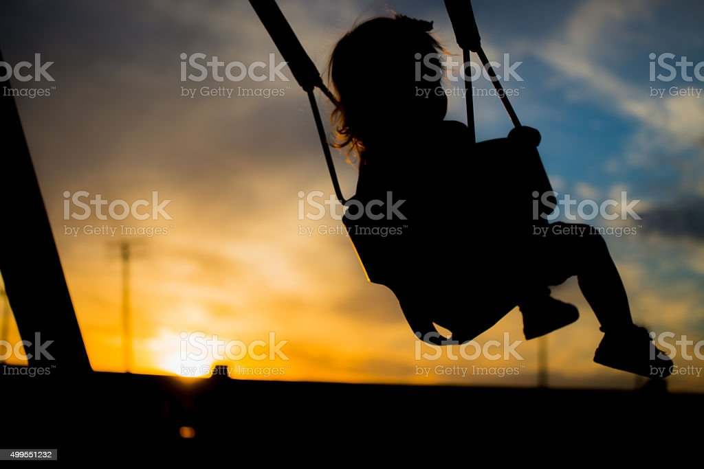 Toddler swinging at sunset (silhouette) stock photo